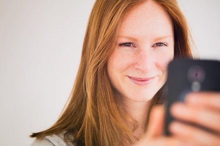 Smiling young woman taking a picture of herself or having a video conversation on her mobile phone.
